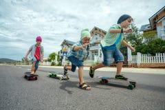 Pojkar på longboardskridskor Arkivbilder