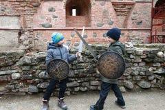 Pojkar slåss med svärd arkivbilder