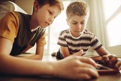 Pojkar som använder minnestavlaPC royaltyfri bild
