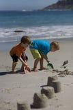 Pojkar som bygger sandslott på stranden arkivbilder