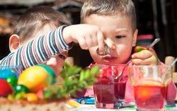 pojkar som färgar easter ägg Arkivfoto