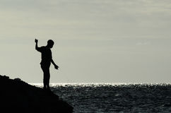 Pojkar som fiskar från stenig kust Fotografering för Bildbyråer
