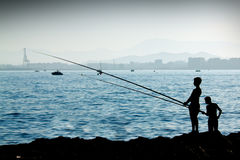 pojkar som fiskar silhouetten Fotografering för Bildbyråer