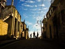 Pojkar som flyger selfmade drakar i en gata i Santiago de Cuba Arkivfoton
