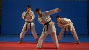 Pojkar som gör uppvärmning och sträcker muskler för karateutbildning på idrottshallen arkivfilmer