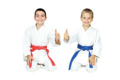 Pojkar som idrottsman nen sitter i en ritual, poserar karate och pekar det toppna fingret Royaltyfri Bild