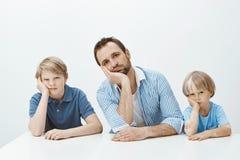 Pojkar som känner sig borrade och förargade Stående av den trötta roliga europeiska familjen av söner och farsasammanträde på tab Royaltyfri Foto