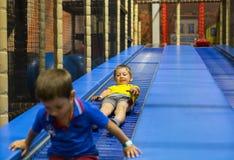 Pojkar som rider glidbanan inom lekplats arkivfoton