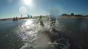 Pojkar som rymmer händer som kör på vattnet arkivfilmer