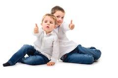 2 pojkar som sitter upp tummar Fotografering för Bildbyråer