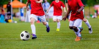 Pojkar som spelar fotbollfotbollsmatchen Internationell sportkonkurrens för ungdomfotbolllag Arkivfoton