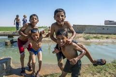 Pojkar som spelar i en bevattningkanal nära Harran i Turkiet royaltyfri fotografi