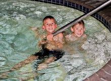 Pojkar som spelar i pöl Royaltyfria Foton
