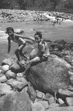 Pojkar spelar i flodbanken fotografering för bildbyråer