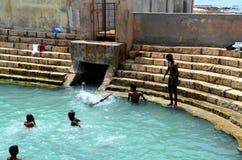 Pojkar spelar och badar i behållare för Keerimalai sötvattenvår vid havvatten Jaffna Sri Lanka arkivfoton