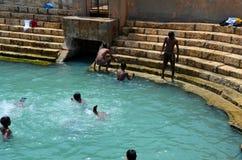 Pojkar spelar och badar i behållare för Keerimalai sötvattenvår vid havvatten Jaffna Sri Lanka arkivbilder