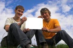 pojkar tar bort papper två Arkivbild