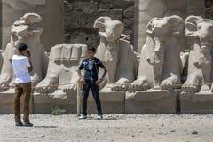 Pojkar tar fotografier framme av stenen sned RAMstatyer på templet av Karnak i Luxor i Egypten Arkivbild
