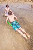 Pojkar tycker om att surfa med ett boogiebräde Fotografering för Bildbyråer