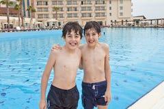 Pojkarna är har gyckel i simbassängen Royaltyfria Foton