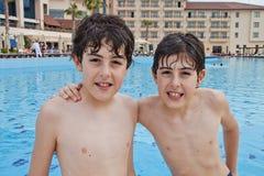 Pojkarna är har gyckel i simbassängen arkivfoto