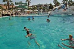 Pojkarna är har gyckel i simbassängen Royaltyfri Bild