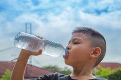 Pojkarna dricker kallt vatten arkivfoto