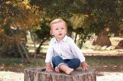 Pojke 1 år gammalt sammanträde på en trädstubbe på en solig sommardag K arkivbilder