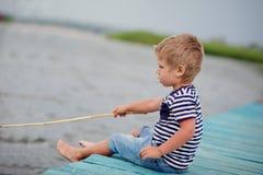 Pojke av fyra på bryggan vid havet Arkivfoton