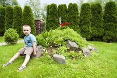 Pojke bland blommor och andra växter royaltyfri fotografi
