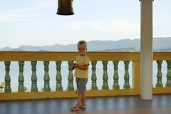 Pojke blont hår och att stå på balkongen som ser kameran mot bakgrund av bergen, hav Royaltyfri Fotografi