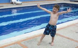 Pojke en utomhus- simbassäng Arkivbild