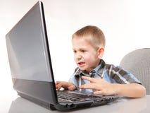Emotionell pojke för datorböjelse med bärbar dator Arkivbilder