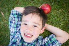 Pojke för kines och för Caucasian för blandat lopp ung med Apple den avslappnande nollan royaltyfria bilder
