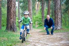 Pojke för liten unge av 3 år och hans fader i höstskog med en cykel Farsaundervisningson Man som är lycklig om framgång Barnhjälm Royaltyfri Bild
