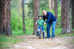 Pojke för liten unge av 3 år och hans fader i höstskog med en cykel Farsaundervisningson Man som är lycklig om framgång Barnhjälm Fotografering för Bildbyråer