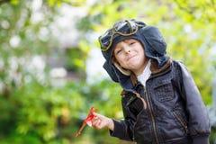 Pojke för liten unge i den pilot- hjälmen som spelar med leksakflygplanet arkivfoton