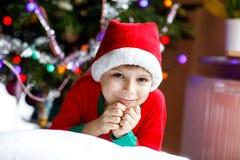 Pojke för liten unge i den santa hatten med julgranen och ljus på bakgrund Royaltyfri Foto