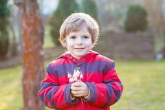 Pojke för liten unge i hållande snödroppe för rött omslag Arkivbilder