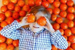 Pojke för liten unge med sunda mandarinfrukter Royaltyfri Foto
