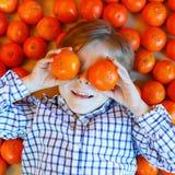 Pojke för liten unge med sunda mandarinfrukter Arkivbild