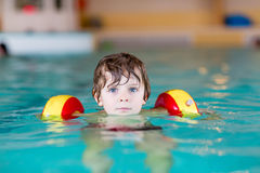 Pojke för liten unge med swimmies som lär att simma i en inomhus pöl royaltyfri bild