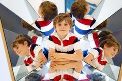 Pojke för liten unge som har gyckel med experiment med speglar i en musem Stående av det lyckliga le skolbarnet Arkivbilder