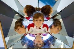 Pojke för liten unge som har gyckel med experiment med speglar i en musem Stående av det lyckliga le skolbarnet Arkivfoto