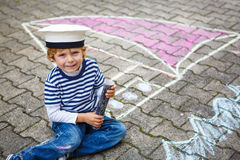 Pojke för liten unge som har gyckel med skeppbildteckningen med krita Arkivbilder