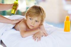 Pojke för liten unge som kopplar av i brunnsort med att ha massage fotografering för bildbyråer