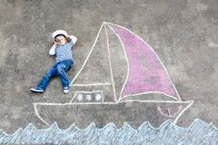 Pojke för liten unge som piratkopierar på skepp- eller sailingboatbildmålning med färgrika chalks på asfalt Fotografering för Bildbyråer