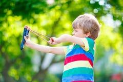 Pojke för liten unge som skjuter träkatapulten arkivfoto