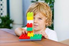 Pojke för liten unge som spelar med plast- kvarter Royaltyfri Bild