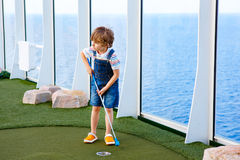 Pojke för liten unge som spelar mini- golf på en kryssningeyeliner Royaltyfri Foto